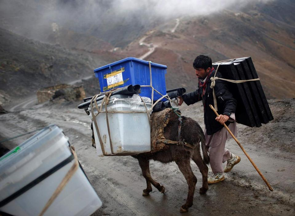 An Afghan man tried Friday to control his donkey loaded with ballot boxes ahead of Saturday's presidential election. They were delivering the supplies to remote villages.