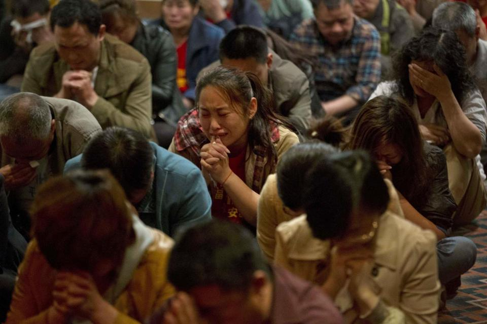 Relatives of those on board the missing plane cried in a prayer room in Beijing on Friday.