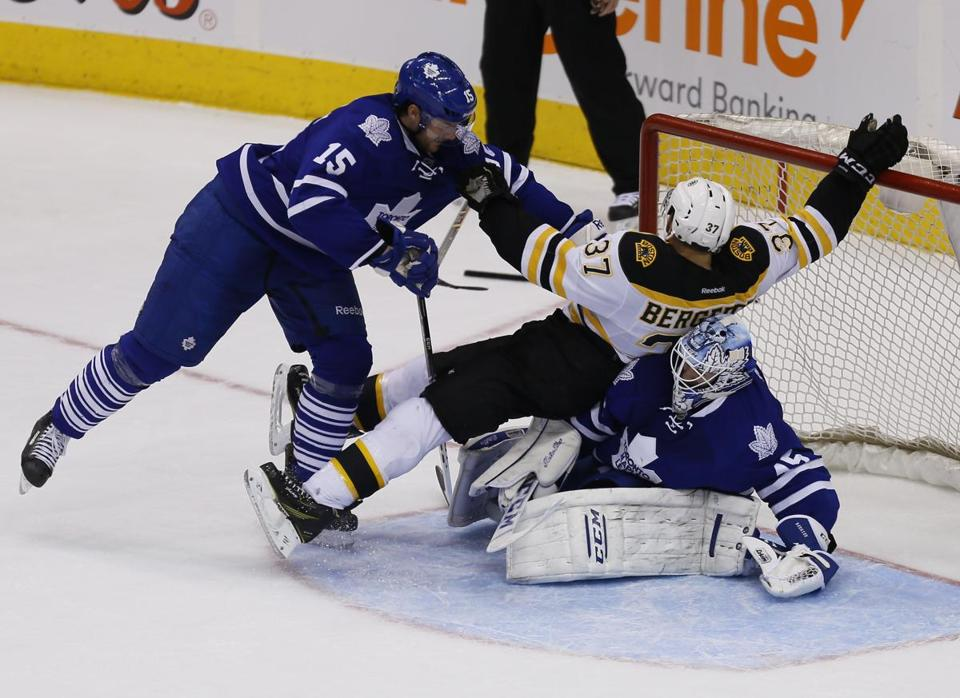 Patrice Bergeron, in the middle of the action, was knocked over goalie Jonathan Bernier, who was injured Thursday.