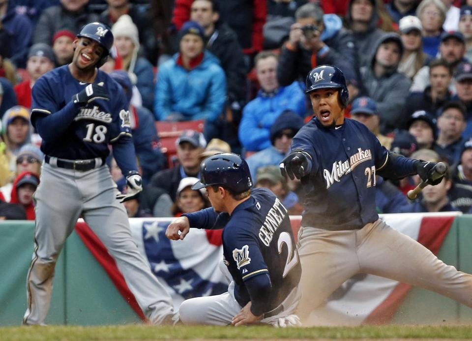Scooter Gennett slides home on Lyle Overbay's double, to the delight of Khris Davis (left) and Carlos Gomez (right). (AP Photo/Elise Amendola)