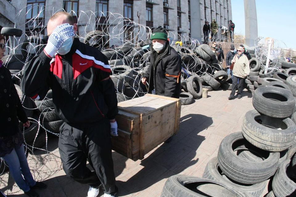 Pro-Russian activists who seized the main administration building in the eastern Ukrainian city of Donetsk carried a box among barricades made of tyres on Monday.