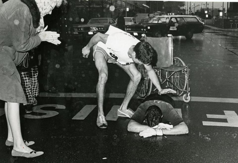"April 20, 1970: At 6:07 p.m., in a chilling, persistent rain, Eugene Roberts, 24, of Baltimore crossed the finish line, almost seven hours after he ""unofficially"" began his remarkable race. Running along with Eugene was his twin brother, James, who drove him with up to Boston. Eugene had both legs amputated after his unit was hit by a howitzer in Vietnam in May 1966."
