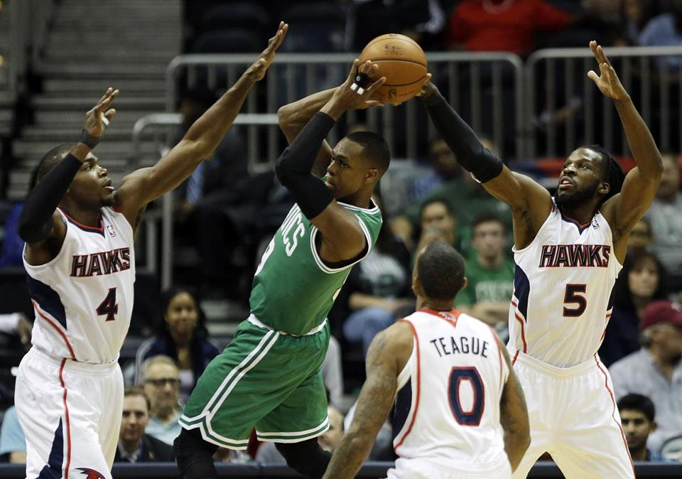 Celtics guard Rajon Rondo looked for some passing options as he was surrounded by Hawks Paul Millsap (4), Jeff Teague (0), and DeMarre Carroll (5).