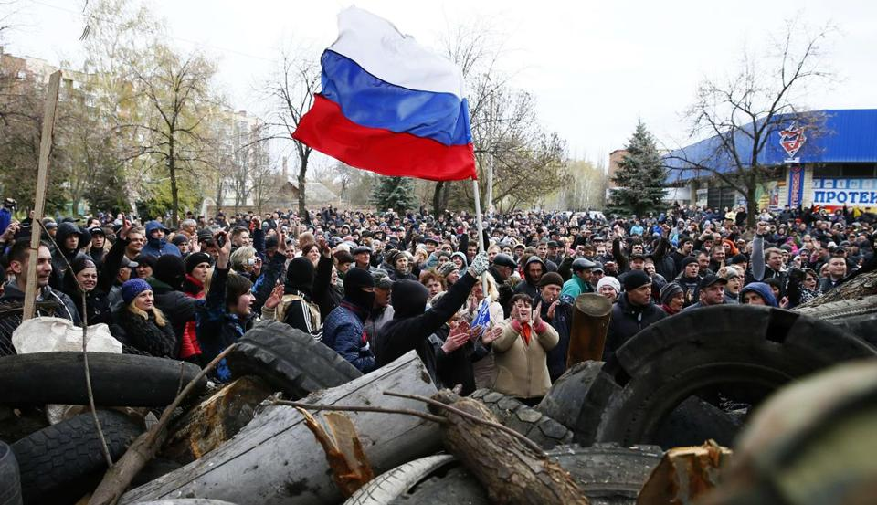 Pro-Russian protestors wave the Russian flag in front of the police headquarters in Slaviansk.