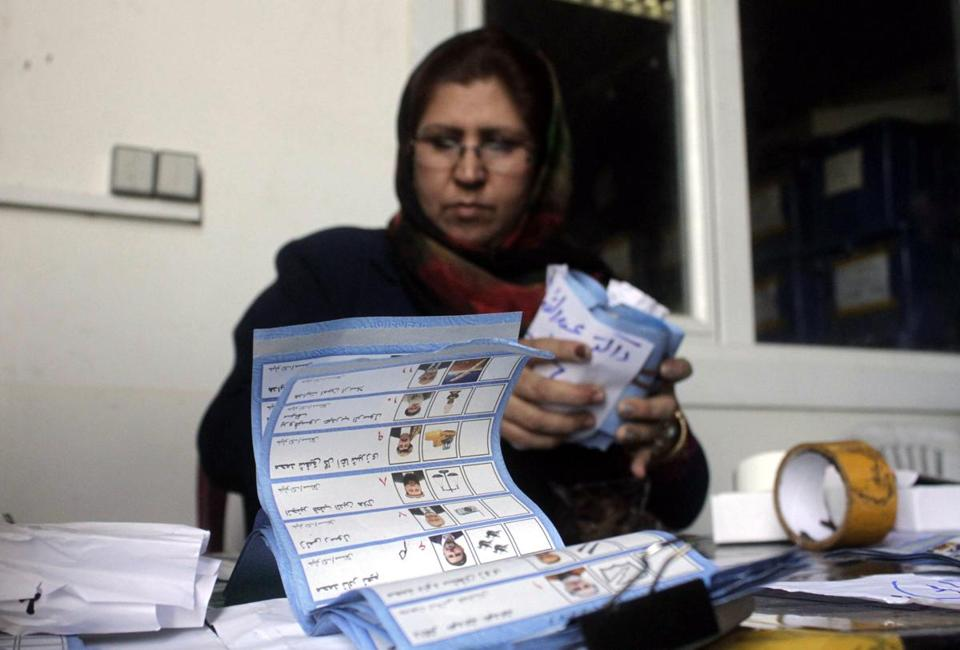 An Independent Election Commission worker tallied ballots Sunday in Kabul.