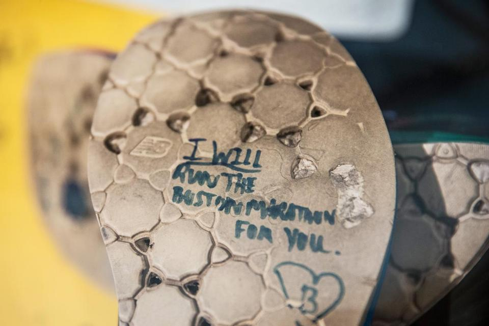 "A runner's shoe, left at the finish line last year, reads ""I will run the Boston Marathon for you."" The shoe is part of a memorial display at the Boston Public Library."