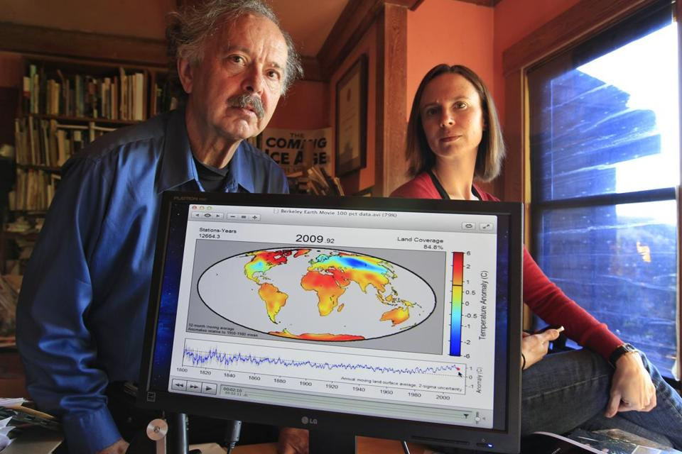 "In this 2011 photo, Richard Muller, left, and his daughter, Elizabeth Muller, right, pose with a map from their study on climate at their home in Berkeley, Calif. Muller is a ""reformed"" climate skeptic."