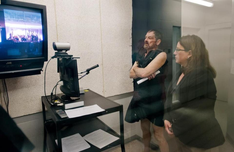 Frazier Glenn Cross appeared at his arraignment by video in New Century, Kansas. On the right is Michelle Durrett, attorney with the public defender's office.