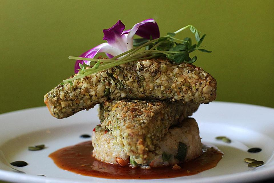 Nutty tofu with green pumpkin seed coating on brown rice risotto cake at Walnut Grille.