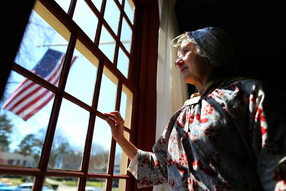 Guide Kathy Eastman looks out a window at Buckman Tavern, where Lexington's militiamen awaited the British in 1775.