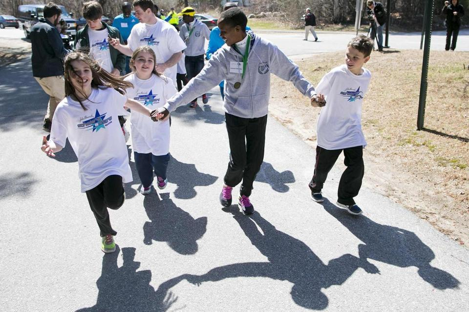 Students join Kenyan elite runner Jemima Sumgong for a lap around the grounds of the Elmwood Elementary School in Hopkinton on Thursday, while Wilson Chebet gets an enthusiastic welcome by second- and third-graders in the school's gymnasium.
