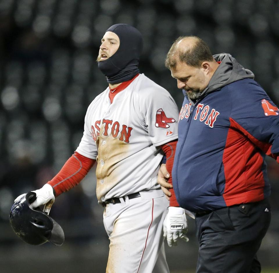 Mike Napoli walks off the field with trainer Rick Jameyson after injuring his left ring finger Tuesday night. Charles Rex Arbogast/Associated Press