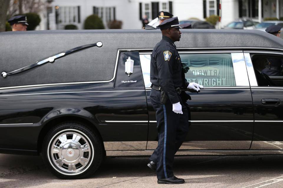 A Boston police officer escorted the hearse carrying the body of Officer DJ Simmonds after his funeral Thursday at Randolph's First Baptist Church.