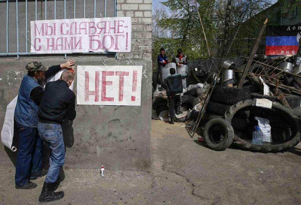 Pro-Russian protesters hung banners on the wall of the house near the barricades at the police headquarters in the eastern Ukrainian town of Slaviansk on Saturday,