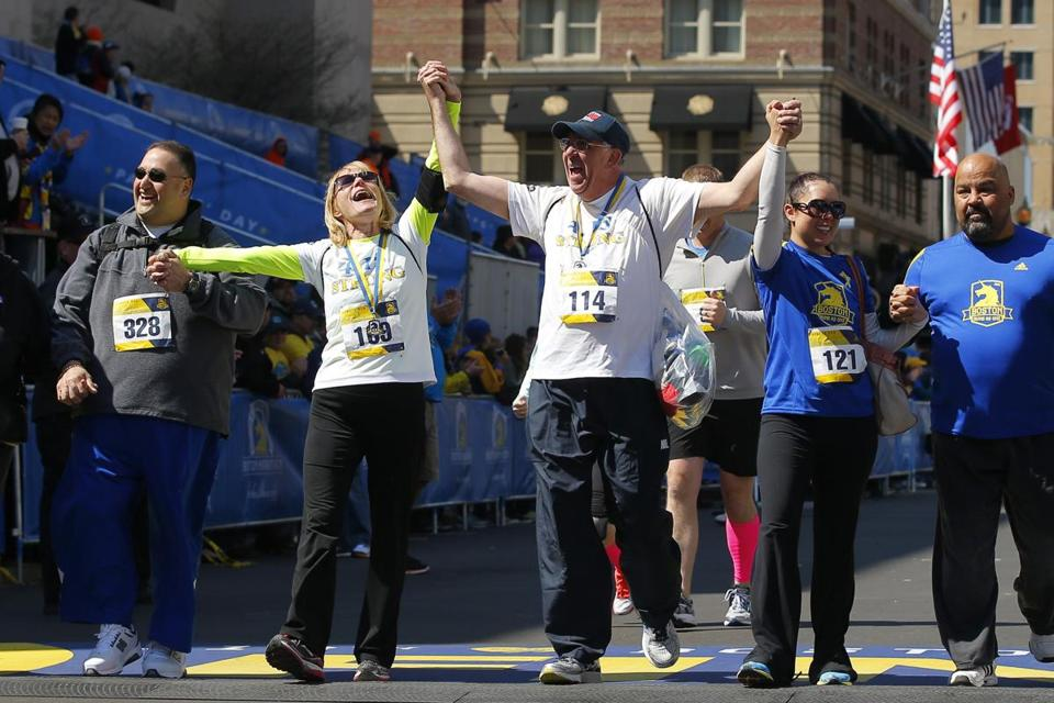 Bombing survivors Beth (second left) and Michael (center) Bourgault crossed the Marathon finish line during a tribute run on Saturday.