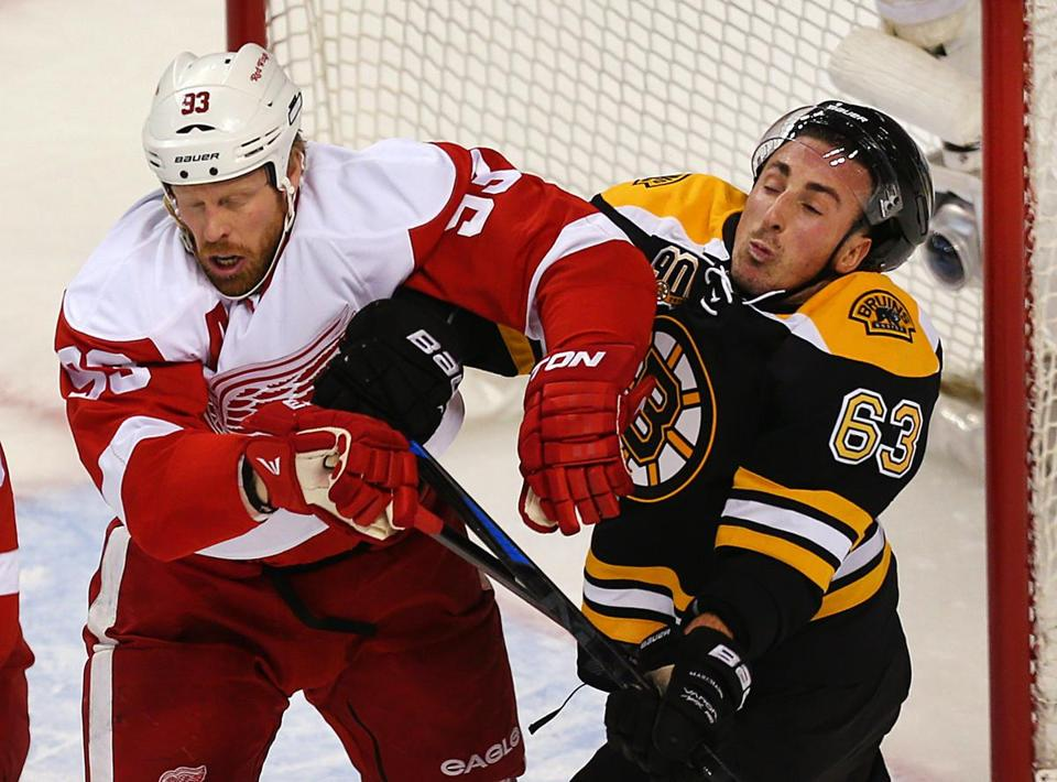Bruins forward Brad Marchand gets physical with the Red Wings' Johan Franzen in front of the Detroit net. (John Tlumacki/Globe Staff)