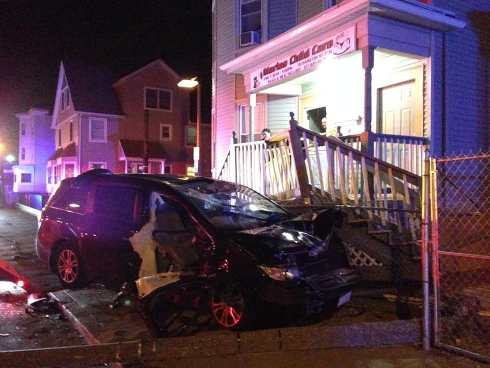 A Honda SUV smashed into the front porch of a building bearing a sign for a child care center.