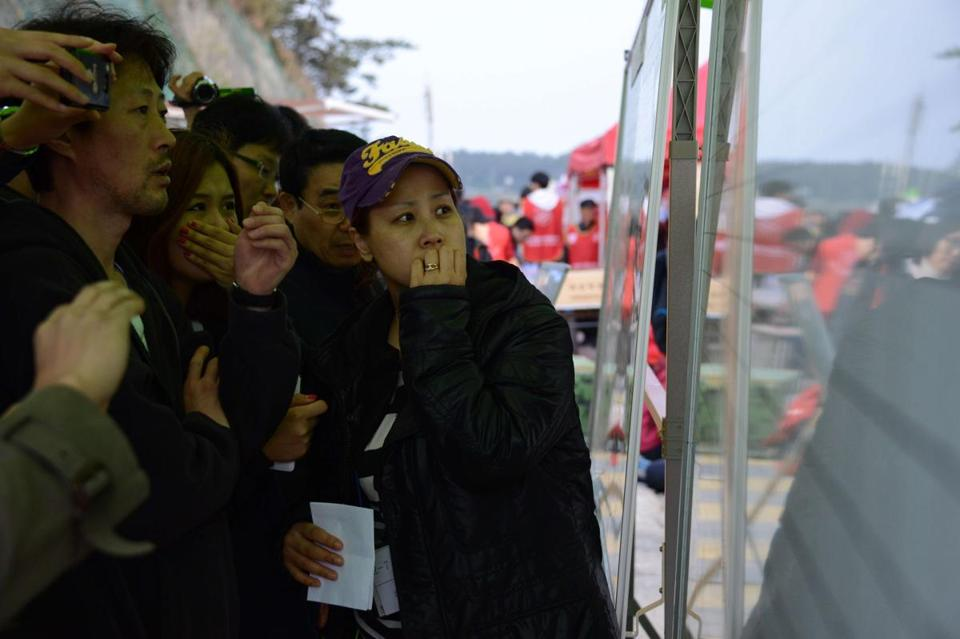 Relatives of those on board the sunken ferry Sewol looked at the names of recovered victims in Jindo, South Korea.