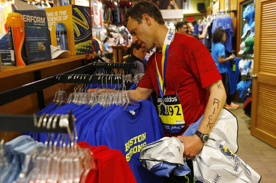 Rick Ginsberg of Denver checked out some Boston Strong T-shirts at Marathon Sports after running the Marathon on Monday.