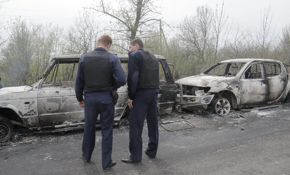 Authorities inspected burnt cars after a deadly shootout at a checkpoint run by pro-Russian militants near Slovyansk, Ukraine.