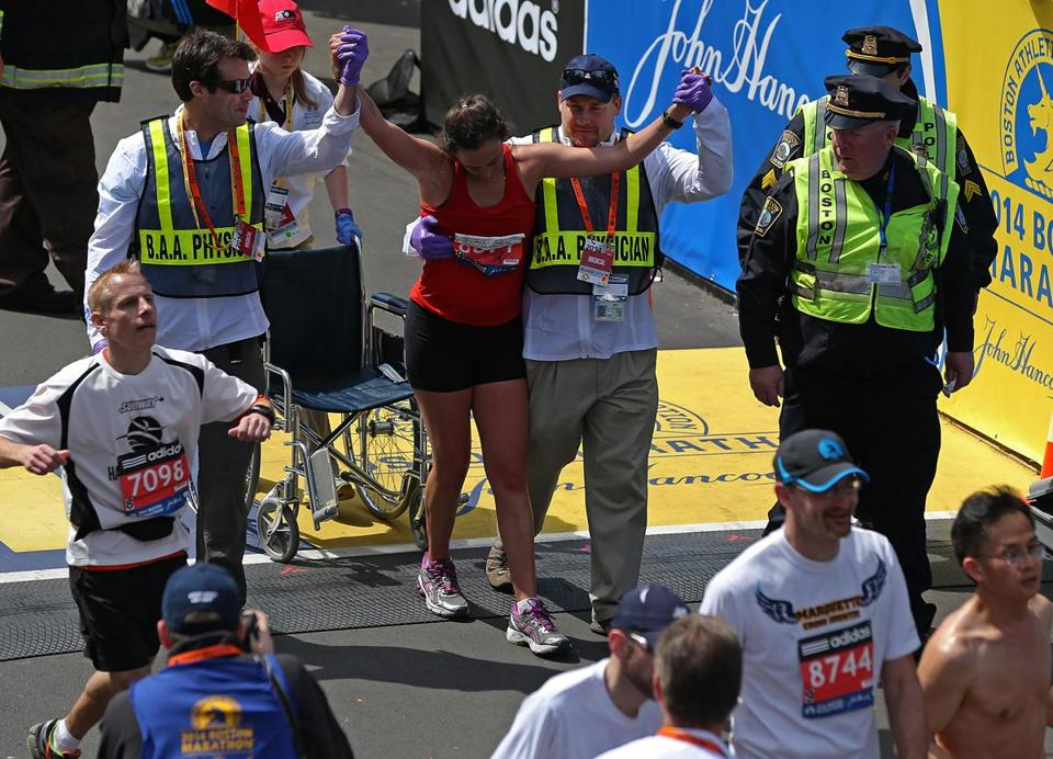 Medical personnel helped a runner at the finish line of the Boston Marathon on Monday.