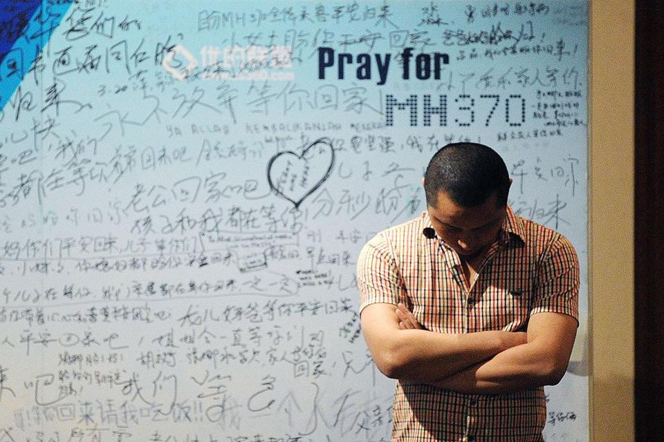 A man stands in front of a memorial billboard for th emissing Malaysia Airlines flight.