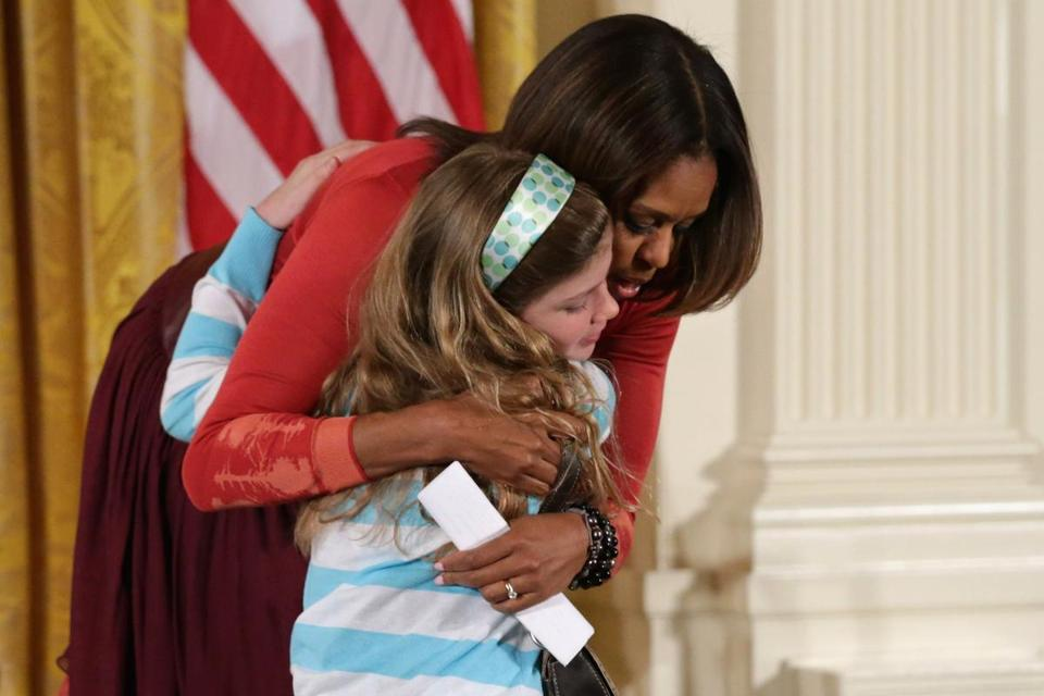 First lady Michelle Obama embraced Charlotte Bell, 10, while hosting a question-and-answer session with the children of Executive Office employees.