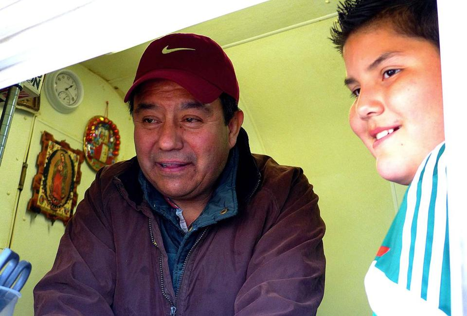 Fermin Fuentes, left, and his nephew Nacho Fuentes wait on customers at Tacos Don Nacho in Pawtucket, R.I.