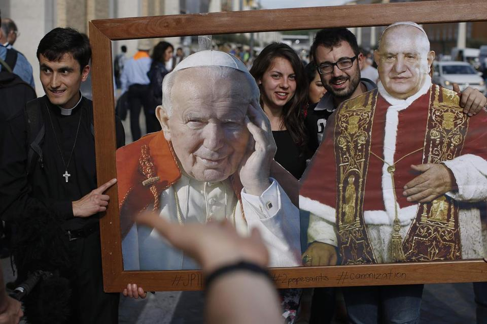 Visitors in Rome posed with photos of Pope John Paul II  and Pope John XXIII. They will be declared saints Sunday.