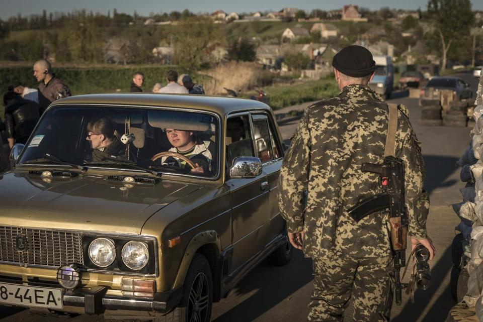 A pro-Russian militant checked a car at a checkpoint on the outskirts of Slovyansk, Ukraine, Friday.