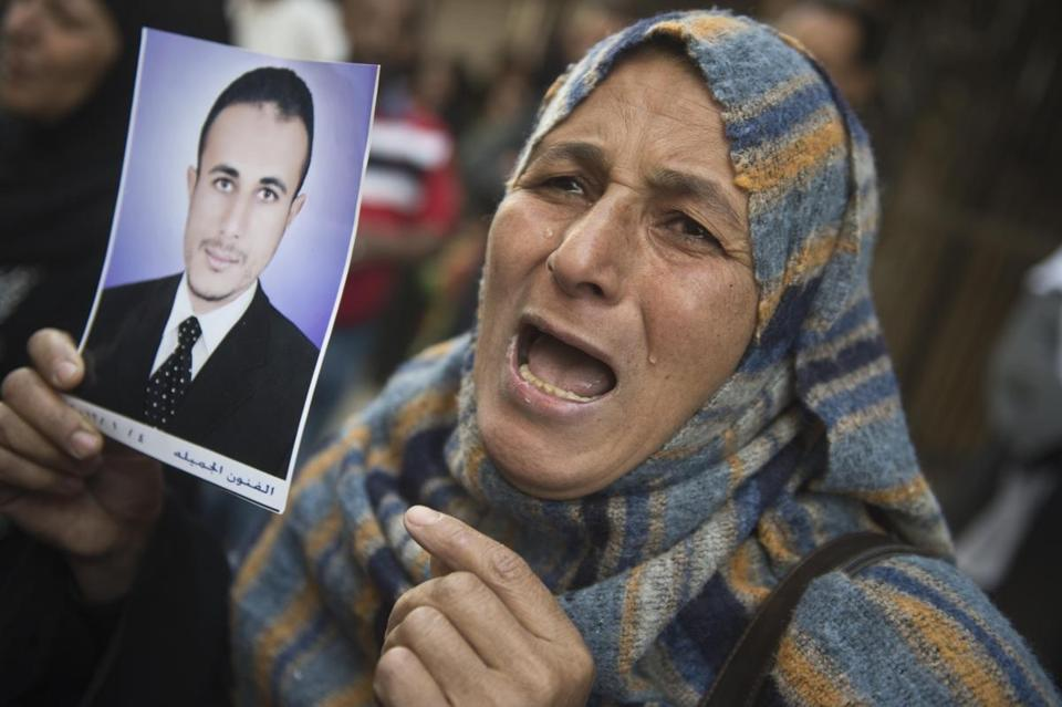An Egyptian woman holding the portrait of a relative reacted after a court that sentenced 682 alleged Islamists and a Muslim Brotherhood leader to death.