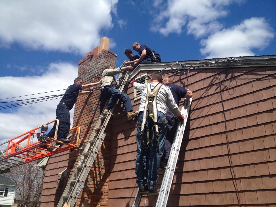 Firefighters discovered the man caught precariously between the rooftop and his ladder, power lines strung around him.