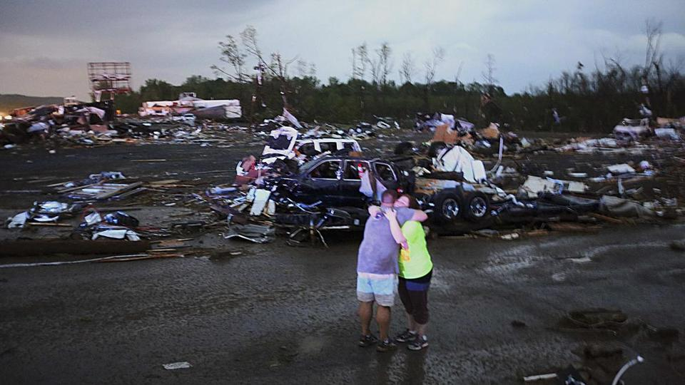 Lori Berseth (right) is consoled after seaching for her missing dog, Lucille, after a tornado destroyed the town of Mayflower, Arkansas.