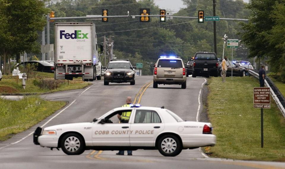 Law enforcement officers respond to a shooting at a FedEx facility in Kennesaw, Ga.