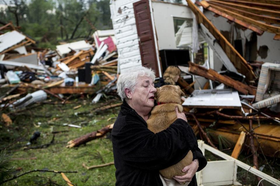 Constance Lambert embraced her dog after finding it alive when she returned to her destroyed home in Tupelo, Miss.