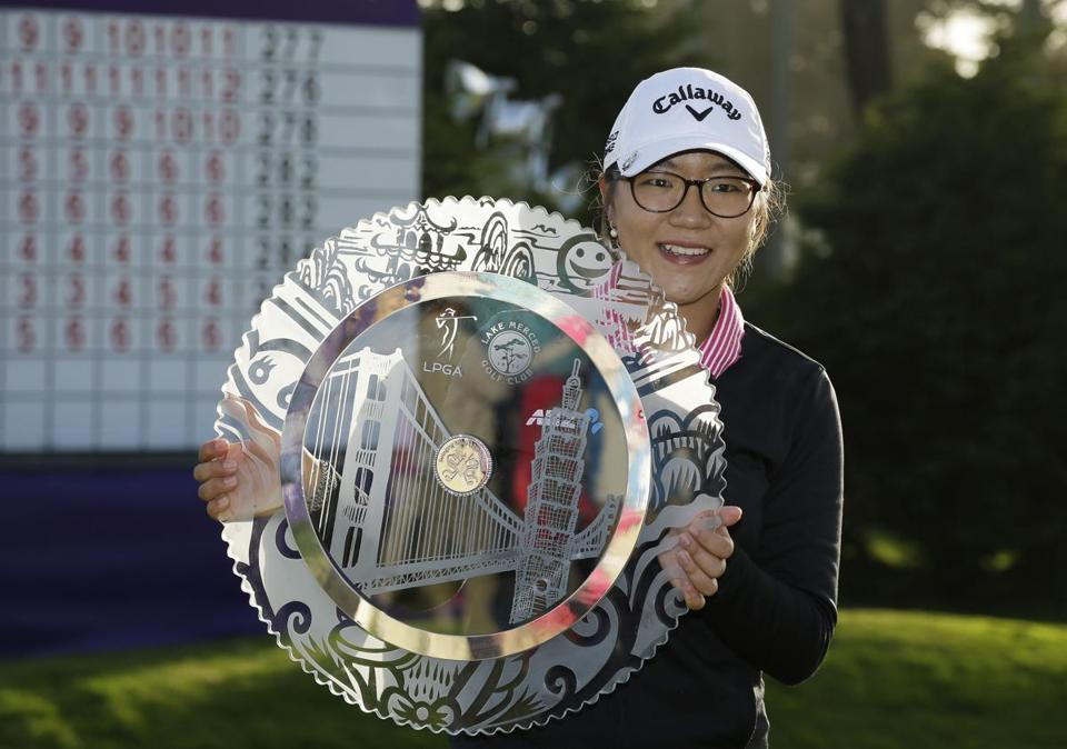 Lydia Ko poses with her trophy on the 18th green after winning the Swinging Skirts LPGA Classic last Sunday.