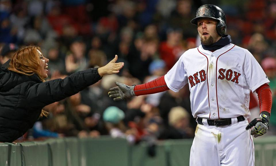 Dustin Pedroia gets a hand from a fan after he scored in the 8th inning.