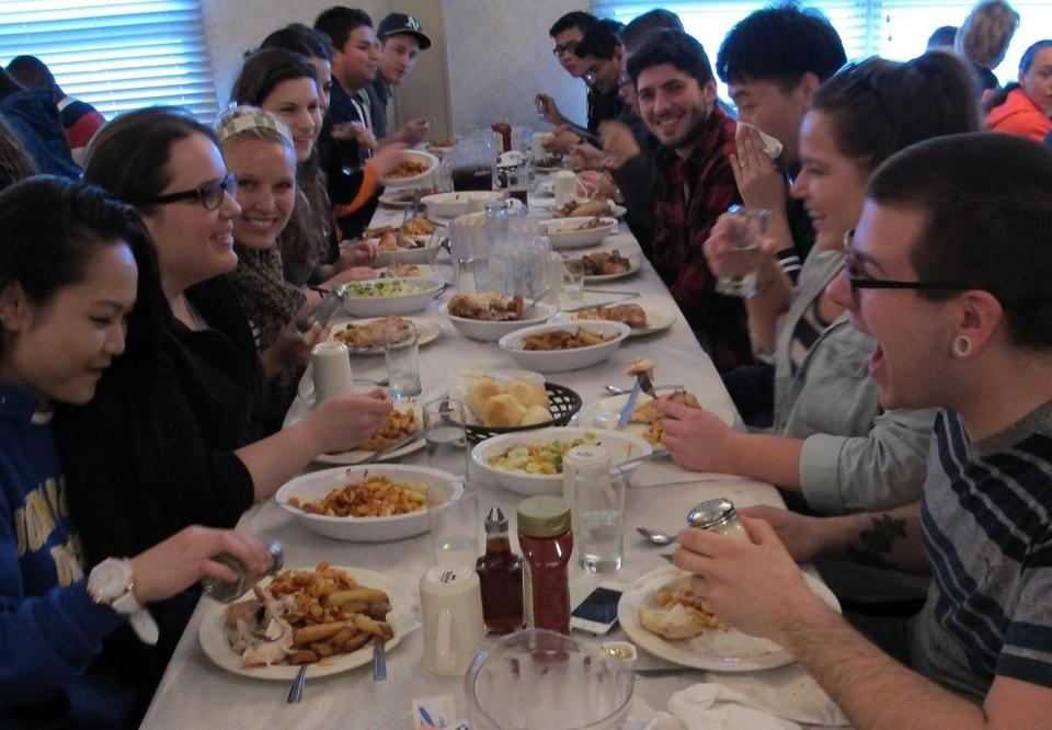 A table of Johnson & Wales students go family-style at Wright's Farm.