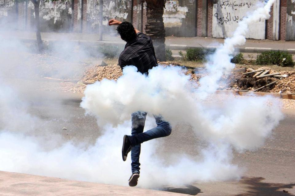 A protester tossed back tear gas during a clash with Egyptian security forces at al-Azhar University on Friday.