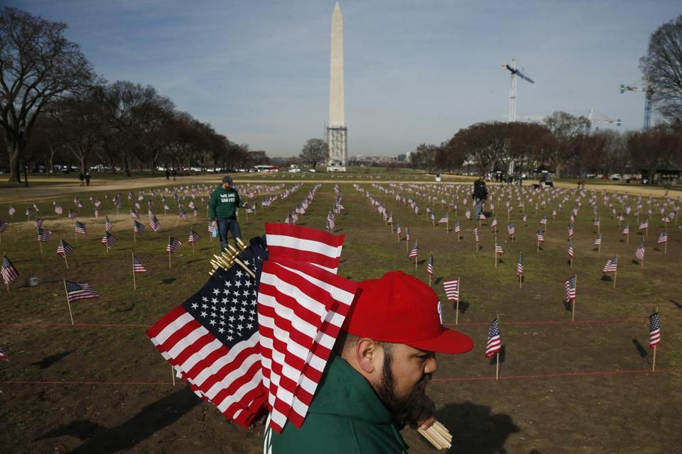 Army veteran Julio Bernal works with others from Iraq and Afghanistan Veterans of America to place 1,892 flags representing veteran and service members who have died by suicide.