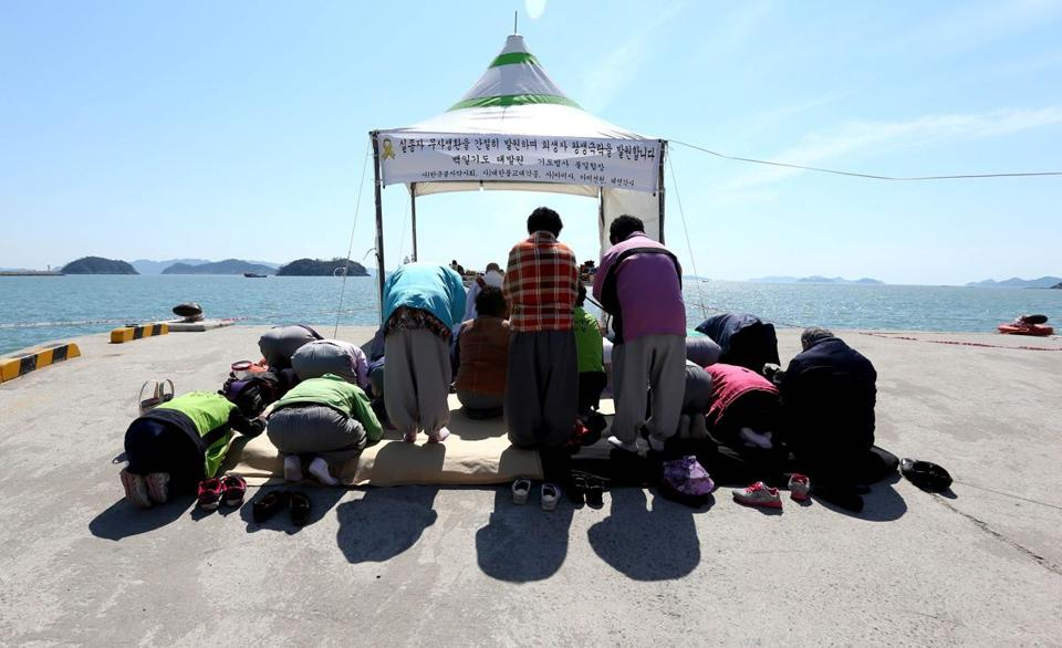 People prayed Tuesday for the ferry's victims at Jindo harbor. A diver who lost consciousness underwater died.