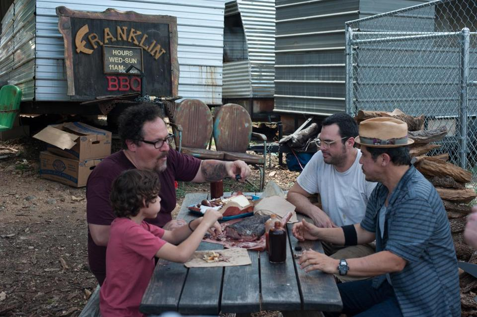 "In a scene from ""Chef,"" (clockwise from left) Emjay Anthony, Jon Favreau, Aaron Franklin, and John Leguizamo at Franklin Barbeque in Austin, Texas."