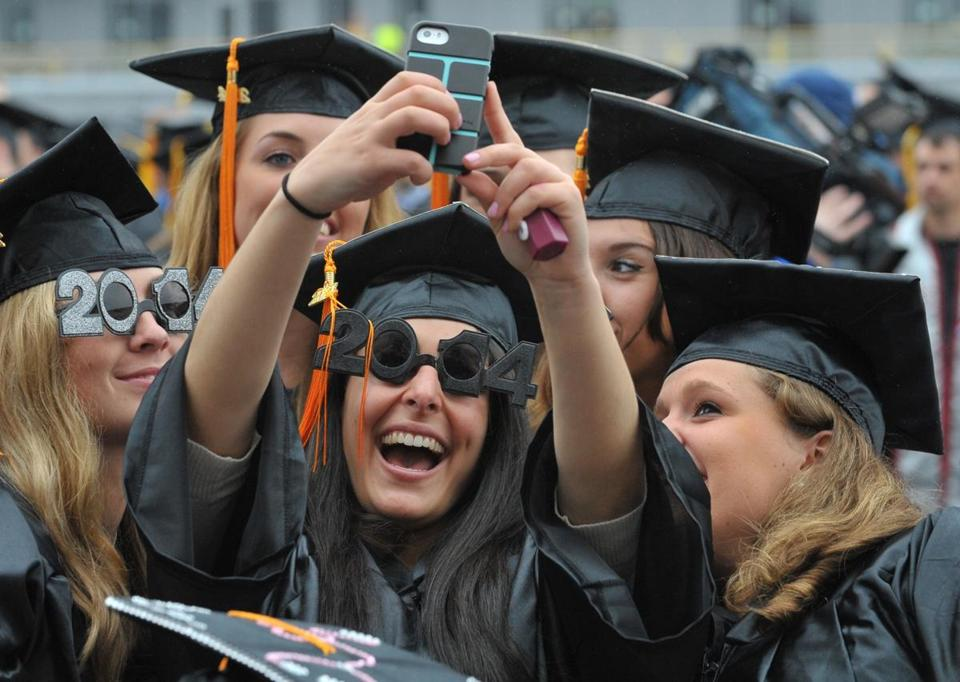 A few UMass Amherst graduates celebrated with a selfie at the start of the 2014 commencement in Amherst  Friday.