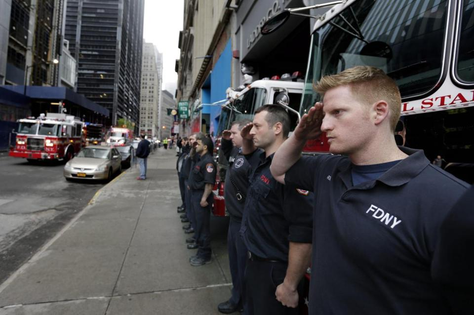 Firefighters saluted the motorcade carrying unidentified remains to a repository at ground zero in New York.