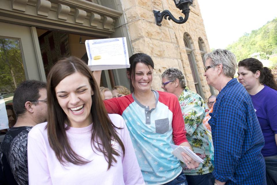 Kristin Seaton held up her marriage license as she left the Carroll County Courthouse with partner Jennifer Rambo.