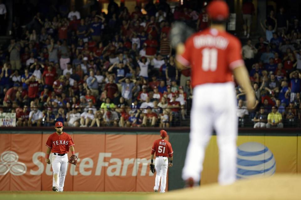 Rangers starter Yu Darvish (11) watches his perfect game fall from the sky when second baseman Rougned Odor (left) and right fielder Alex Rios (51) couldn't come up with David Ortiz's popup in the seventh inning Friday night. (AP Photo/Tony Gutierrez)