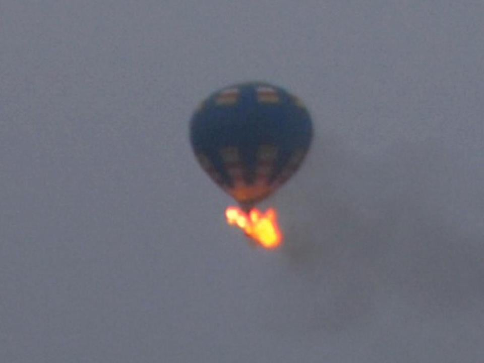A bystander photographed a hot air balloon that caught fire and crashed in Virginia on Friday.