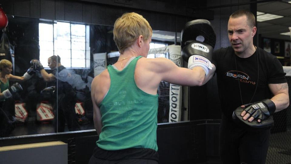 Client Tara Mardigan works out with trainer Kevin Kearns at Sityodtong Muay Thai Academy in Somerville.