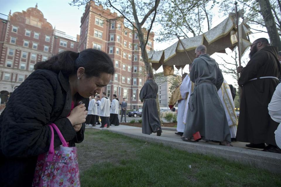 Diana Sanez of Framingham kneeled to pray as the Eucharist passed near the MIT Chapel Monday in response to the black mass controversy. A student club said it decided on its own to call off the event.