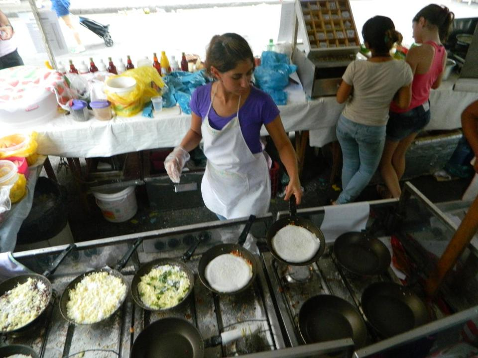 A vendor at an outdoor food market prepares tapioca crepes. A chef may be working 10 pans.